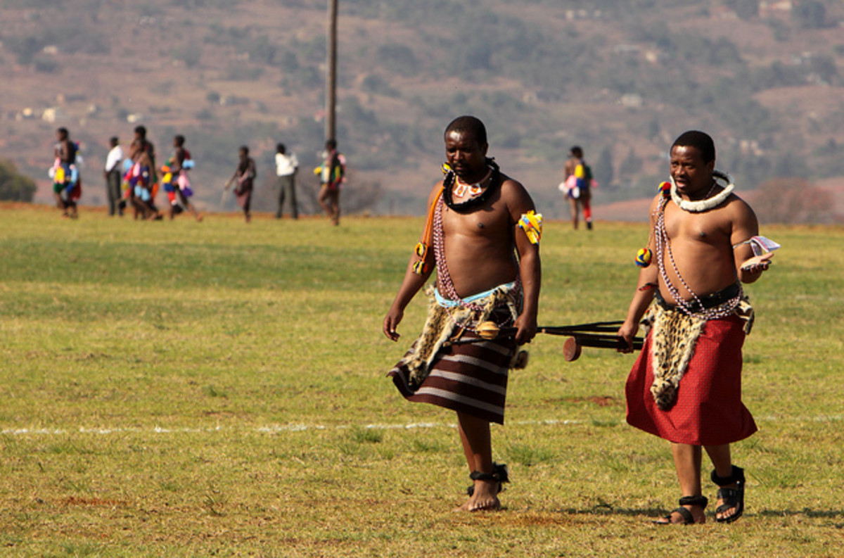 Swazi men corning their traditional wear and necklaces, carrying their cultural sticks on their way to a Swazi Reed festival