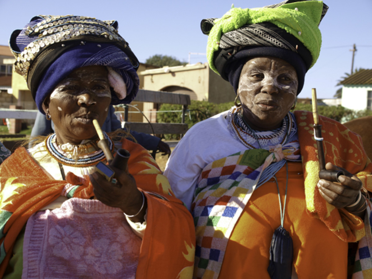 Xhosa women in their traditional attire smoking their trademark pipes