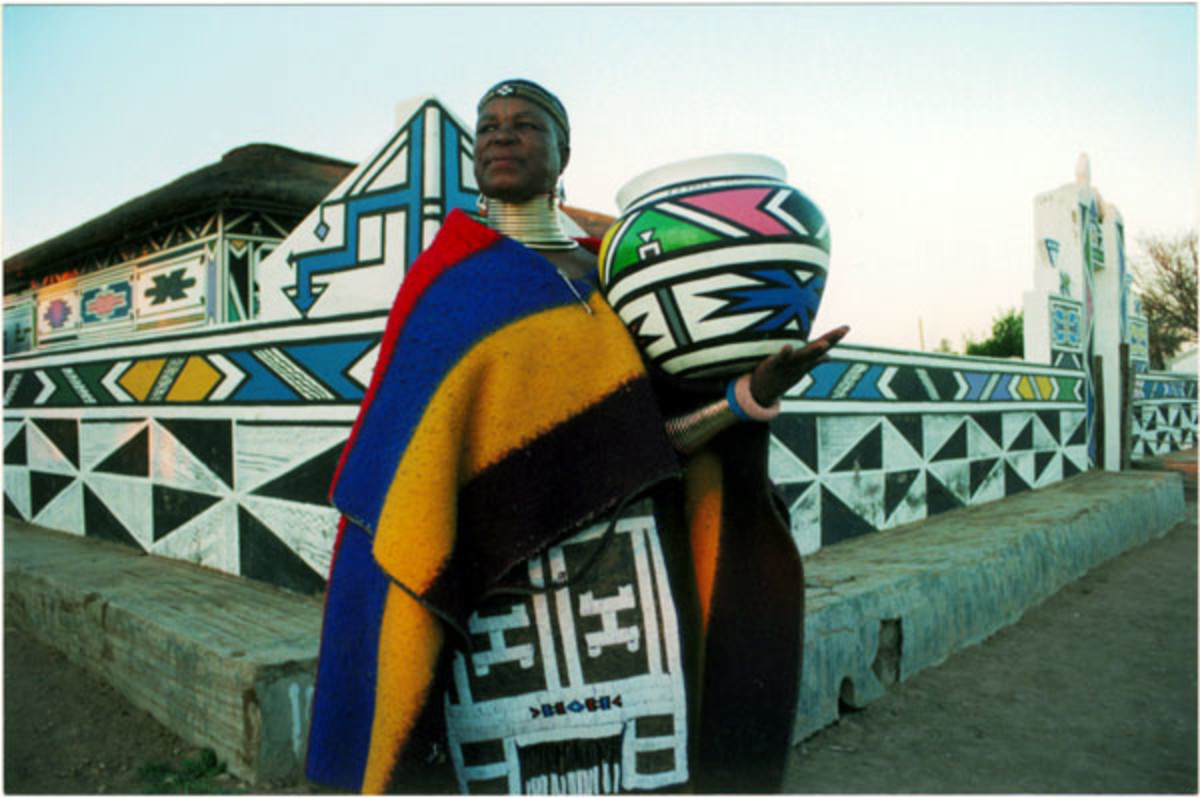 Ndebele Woman Infront of her art decr=orated House, and holding an African Calabash decorate, adorning her cultural Garb... Culture Galore...