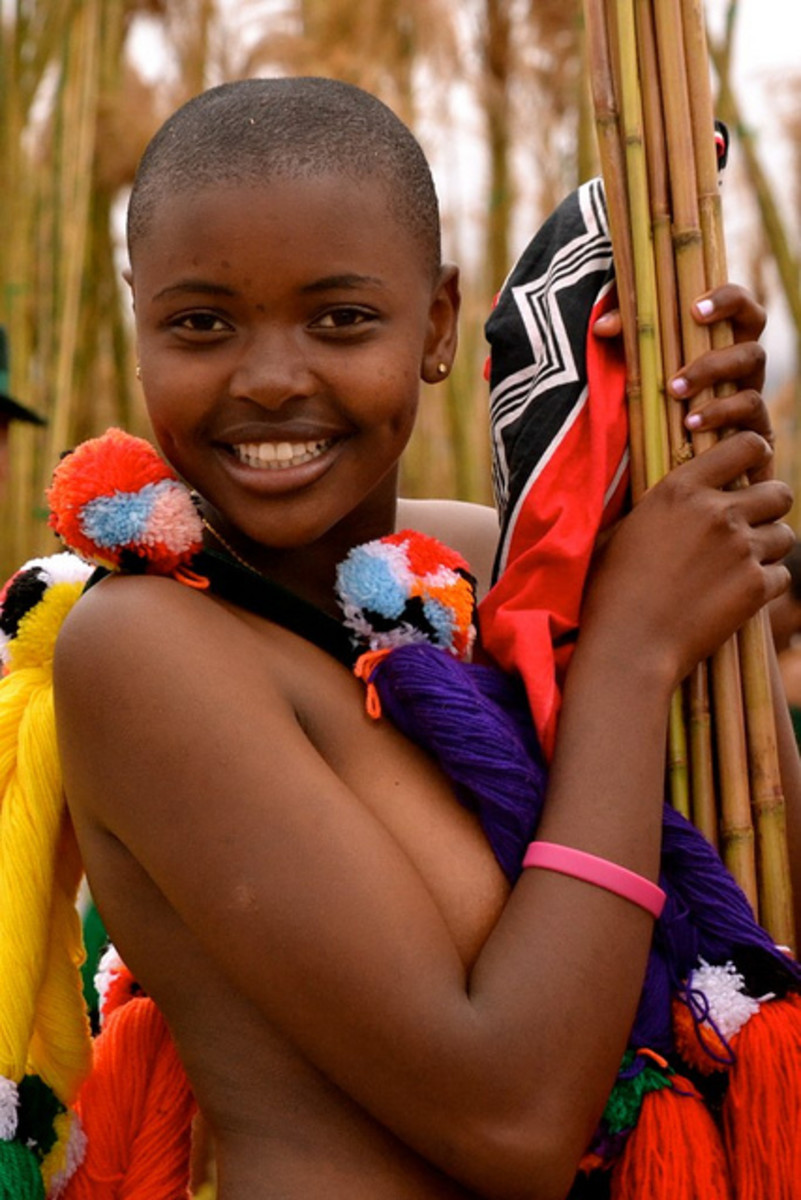 Young and pretty Swazi girl holding her Reeds, and adorned in her cultural garb