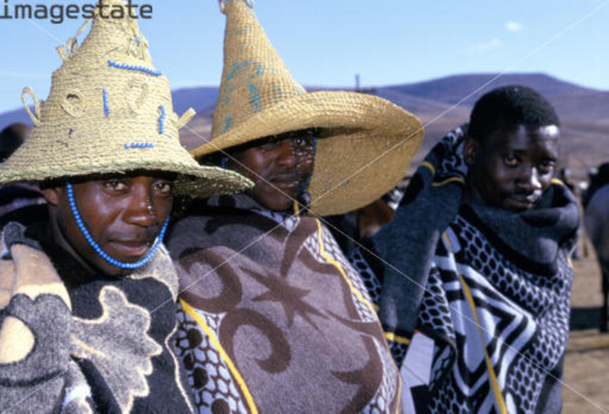 Basotho Men tightly clad in their blankets and corning their traditional hats