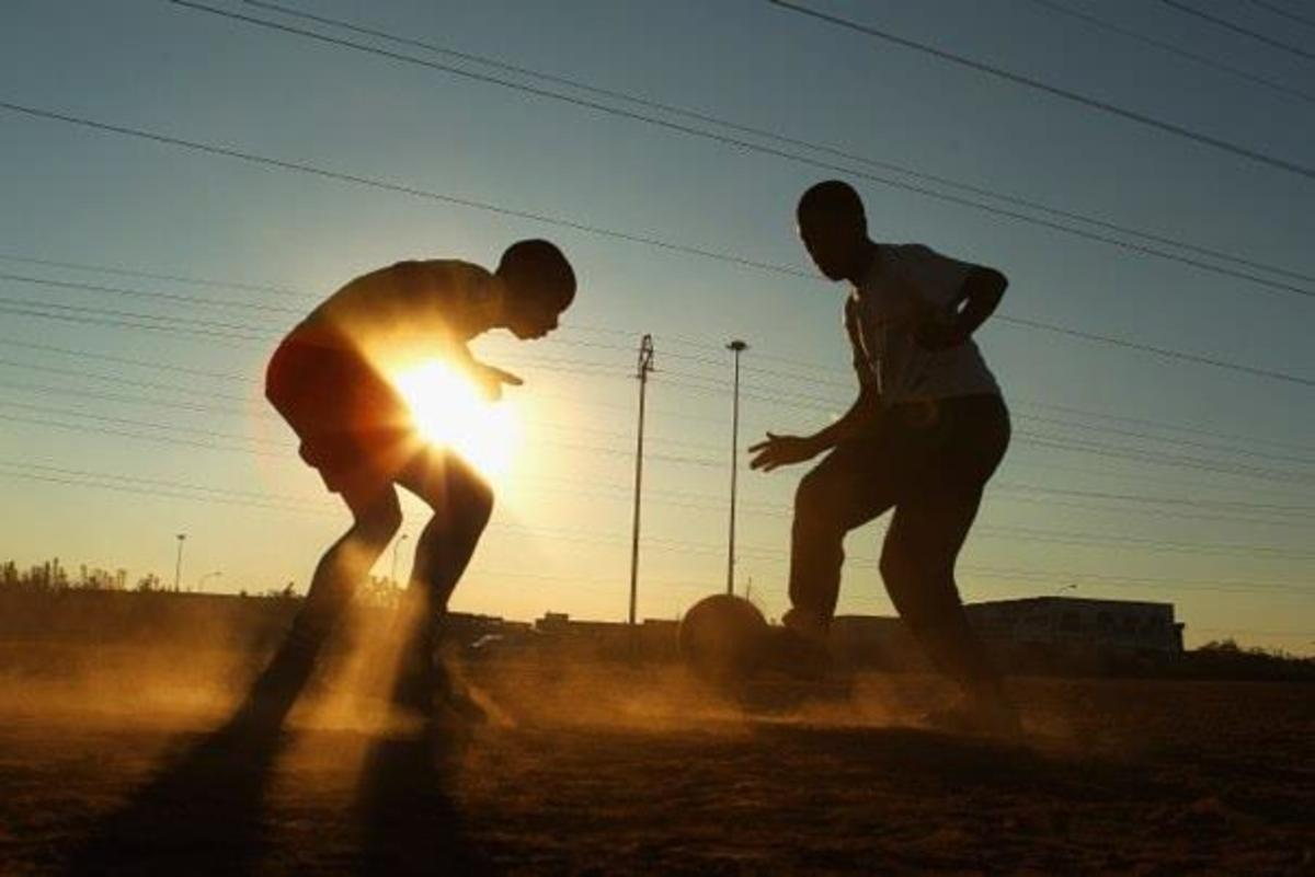 Barefooted and Dribbling-In The Dust and At Dusk.. Soccer Is A Way Of Life Of The Poor In South Africa