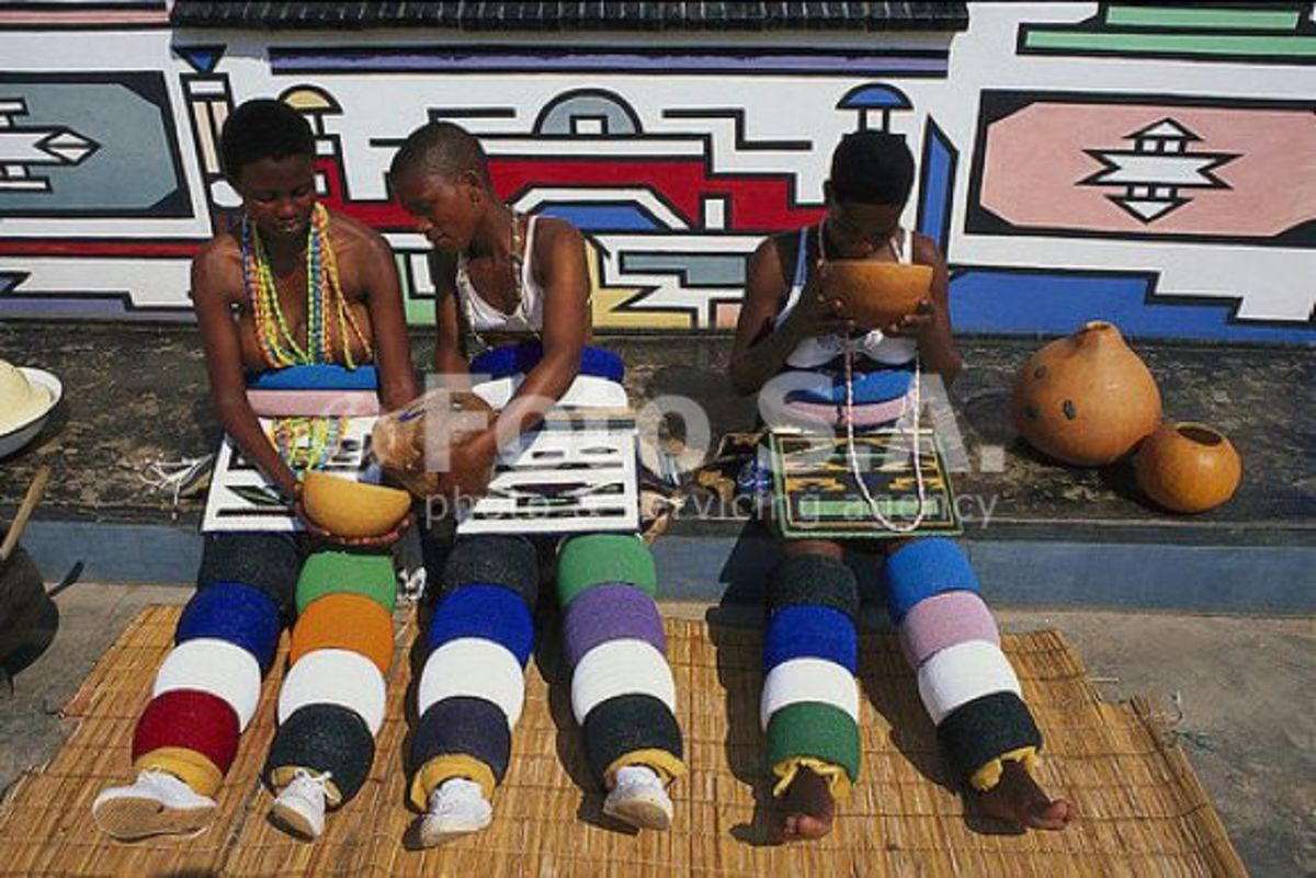 Ndebele girls in their traditional clothing and sitting next to their house they decorated themselves