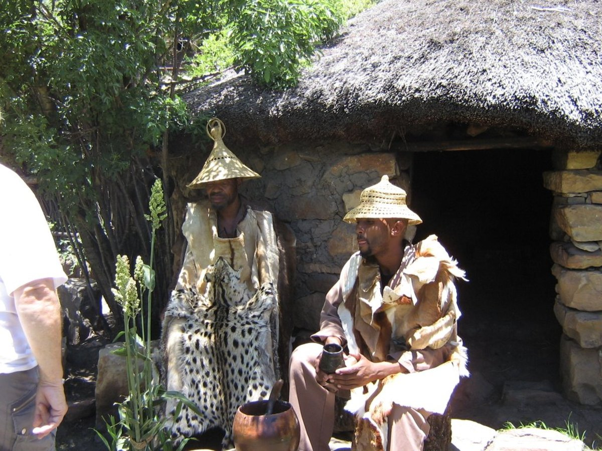 Basotho Men in their traditional hats an dress sitting next to a calabash