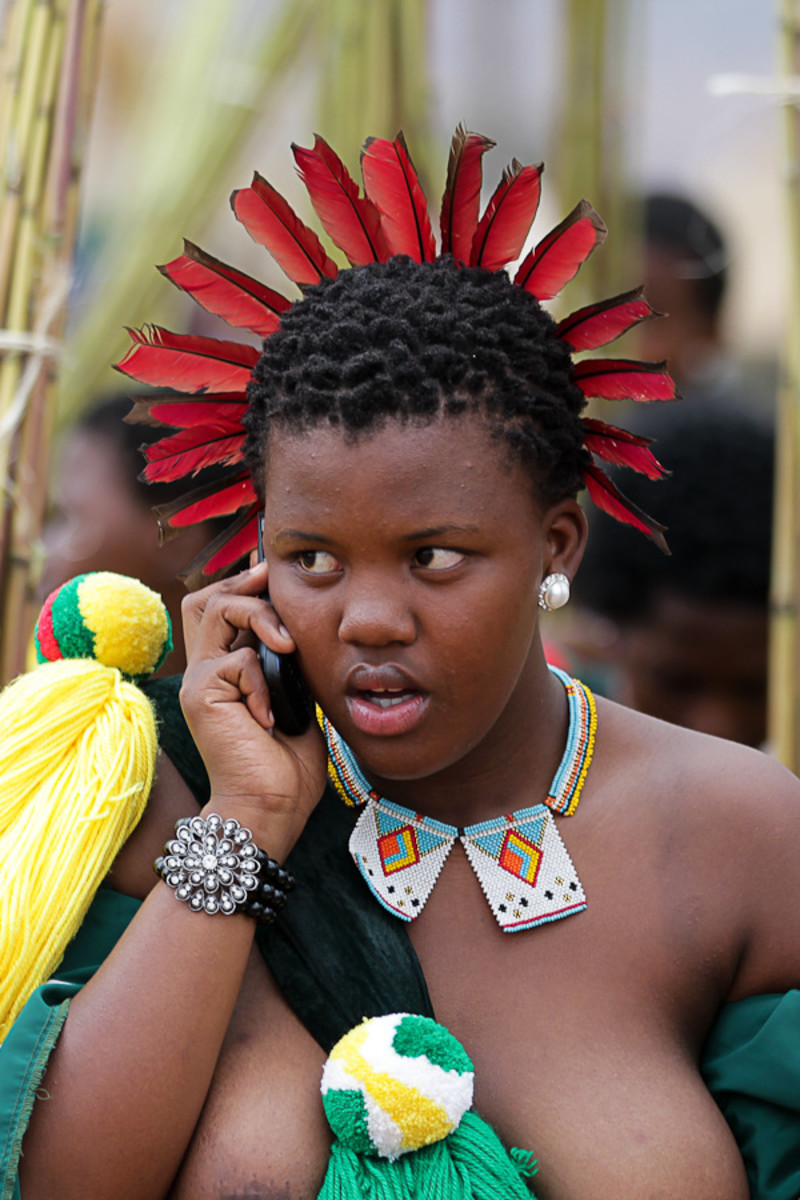 Swazi Girl in her traditional adornment and with a cell phone to go with that too. African Culture meets modernity