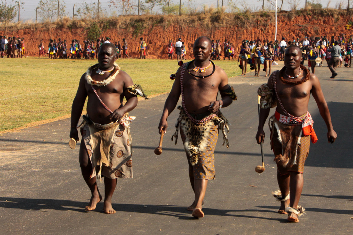Swazi men in traditional garb and accessories marching to the Reeds festivities