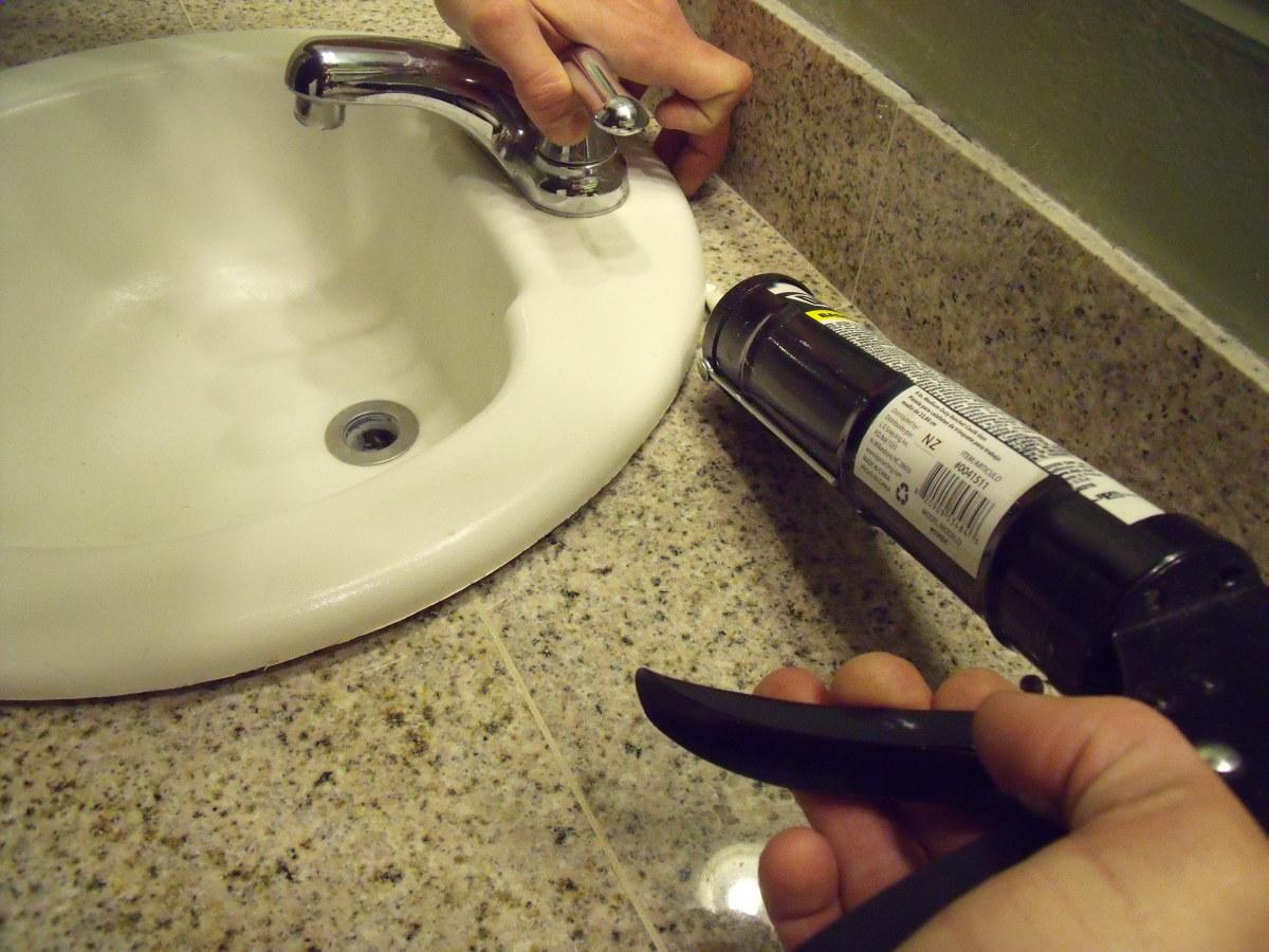Use a caulking gun to apply silicone caulk around the sink.
