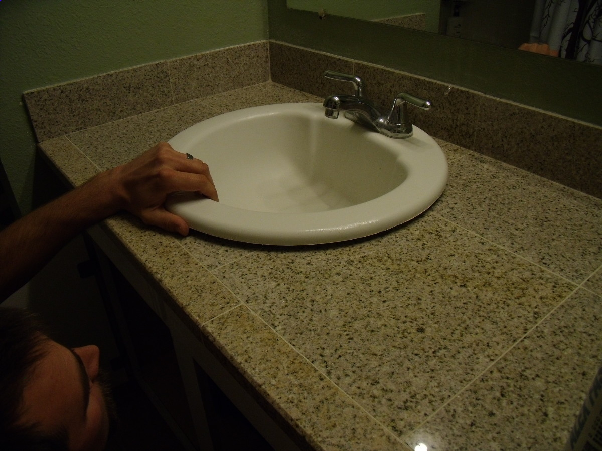 Replace the sink after sealant has cured.