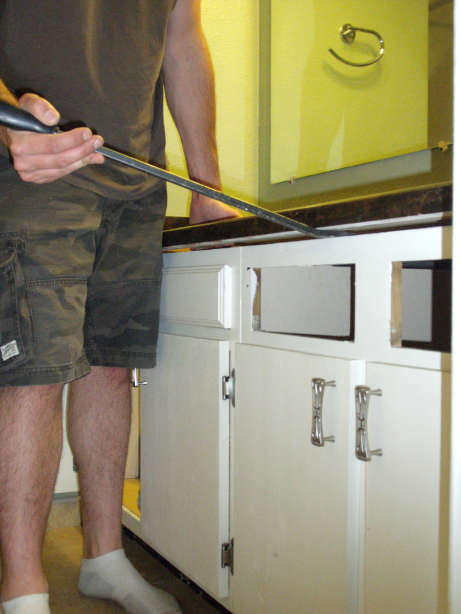 Use a pry bar to pry the countertop from the cabinets.