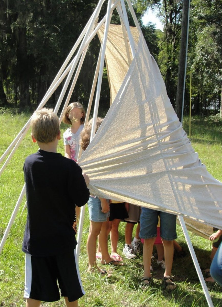 Constructing a tepee using PVC pipe, rubber bands, and a sheet