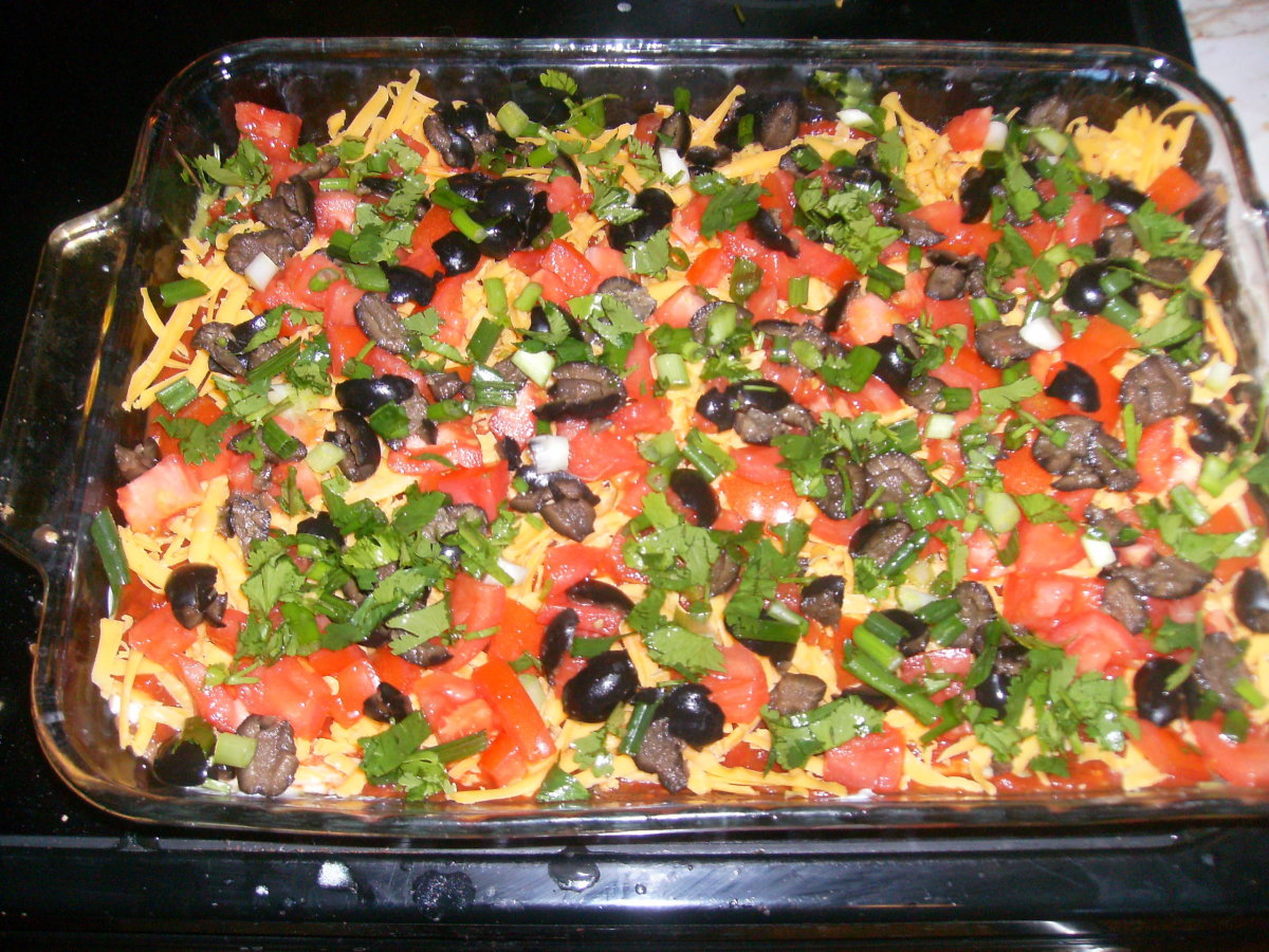 The tomatoes, green onions, and cilantro on top of the cheese and black olives make the dip quite attractive.