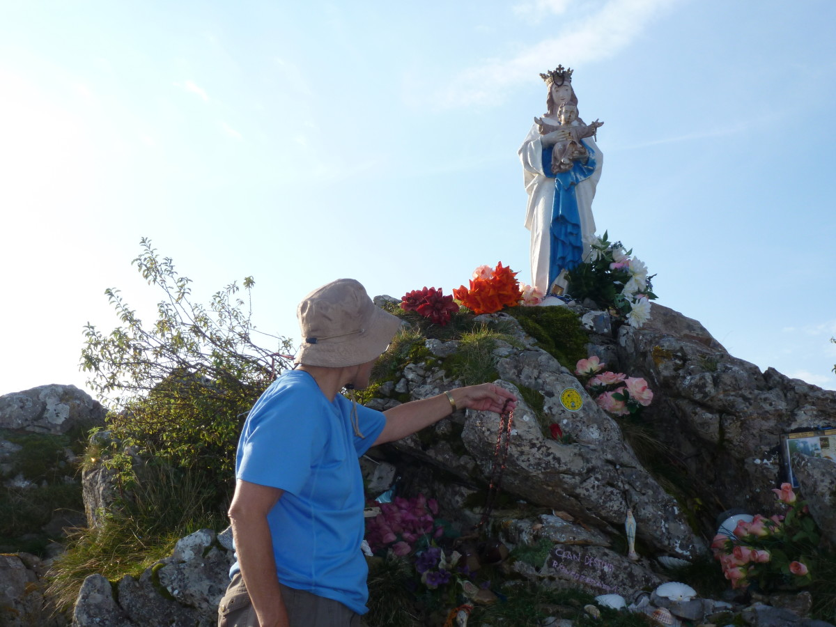 Adding a stone and a prayer to the shrine of the Virgin Mary.