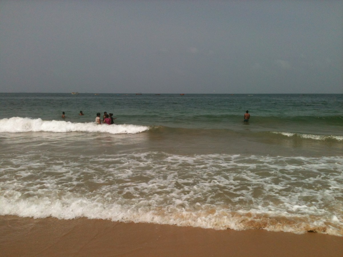 Young men and women enjoying a dip in the sea at Candolim Beach in Goa.