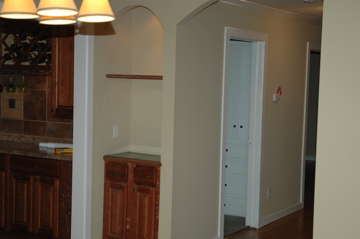 A deep wall in the hallway was opened up to create display space next to the kitchen.