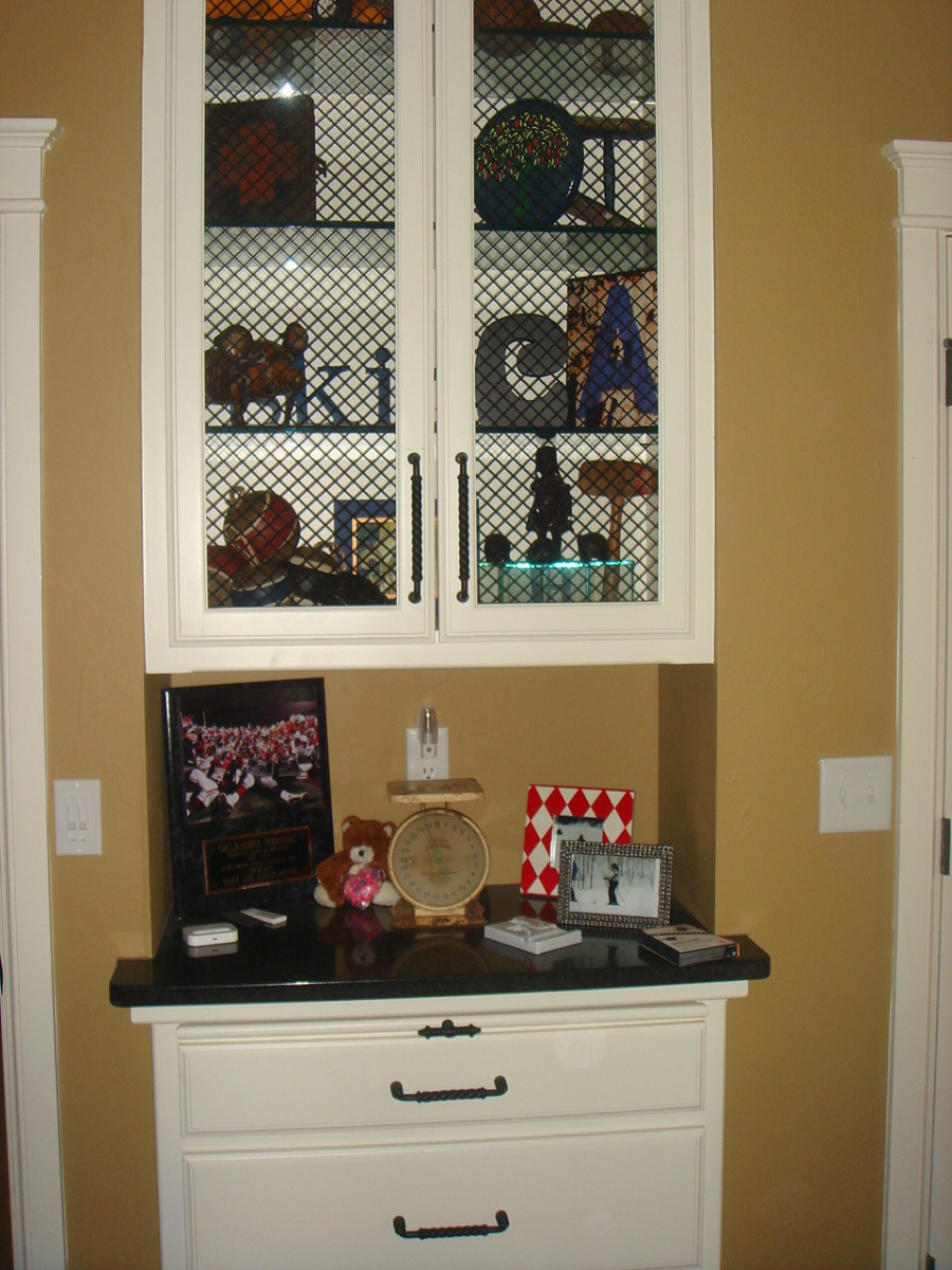 Linen closet in adjacent bath was reduced to add display space in a bedroom.  Chicken wire was used for the cabinet doors.