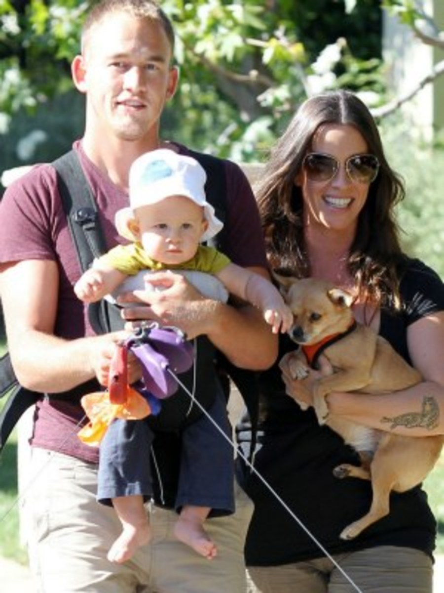 Alanis Morissette and Ever Treadway. Her husband is holding their child, while also wearing it.