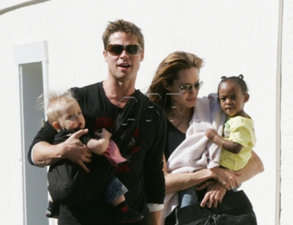 Brad Pitt wearing his baby. Angelina Jolie carrying her child.