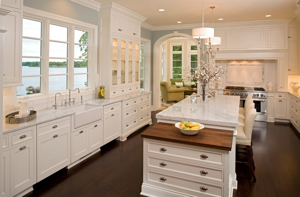 glass cabinet door add character to a classic white kitchen - accented with wood flooring and arched door ways