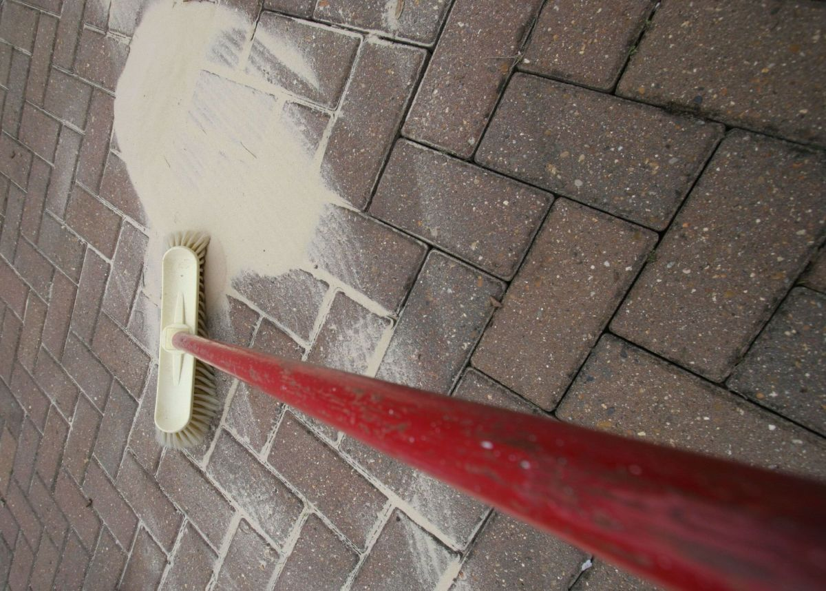 A long-handled brush can make the process of scrubbing algae off a roof much easier.