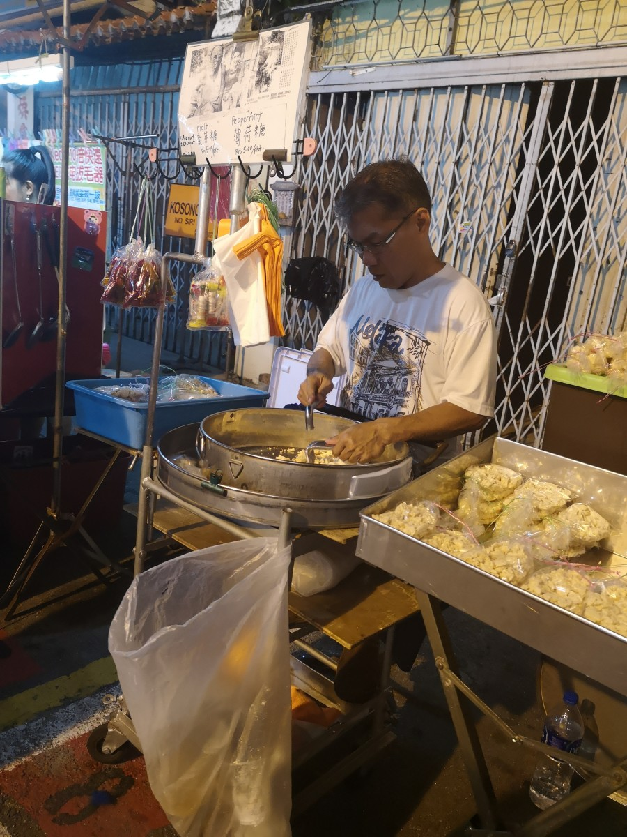 Street vendor preparing the Ding Ding Candy (a hard maltose candy with sesame and ginger flavours)