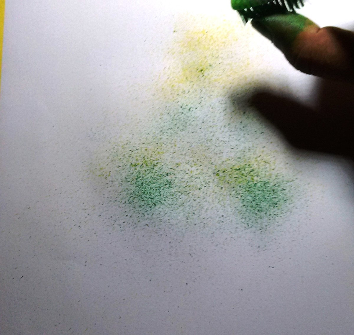 Spray the green paint below the yellow colors.