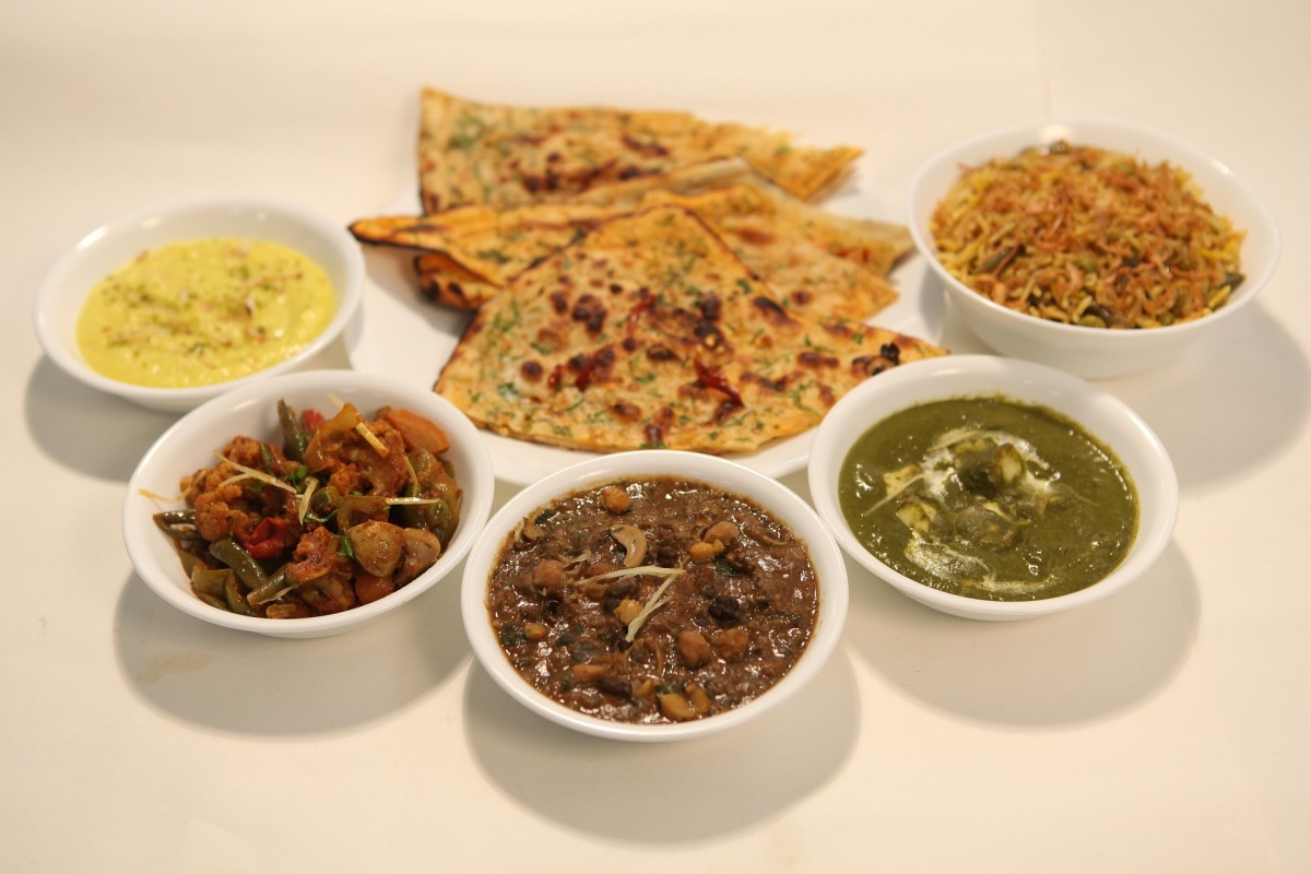A Thali (pictured above), typically served in a round style or round plate, consists of choices of vegetable dishes along with buttered Indian bread and other condiments.