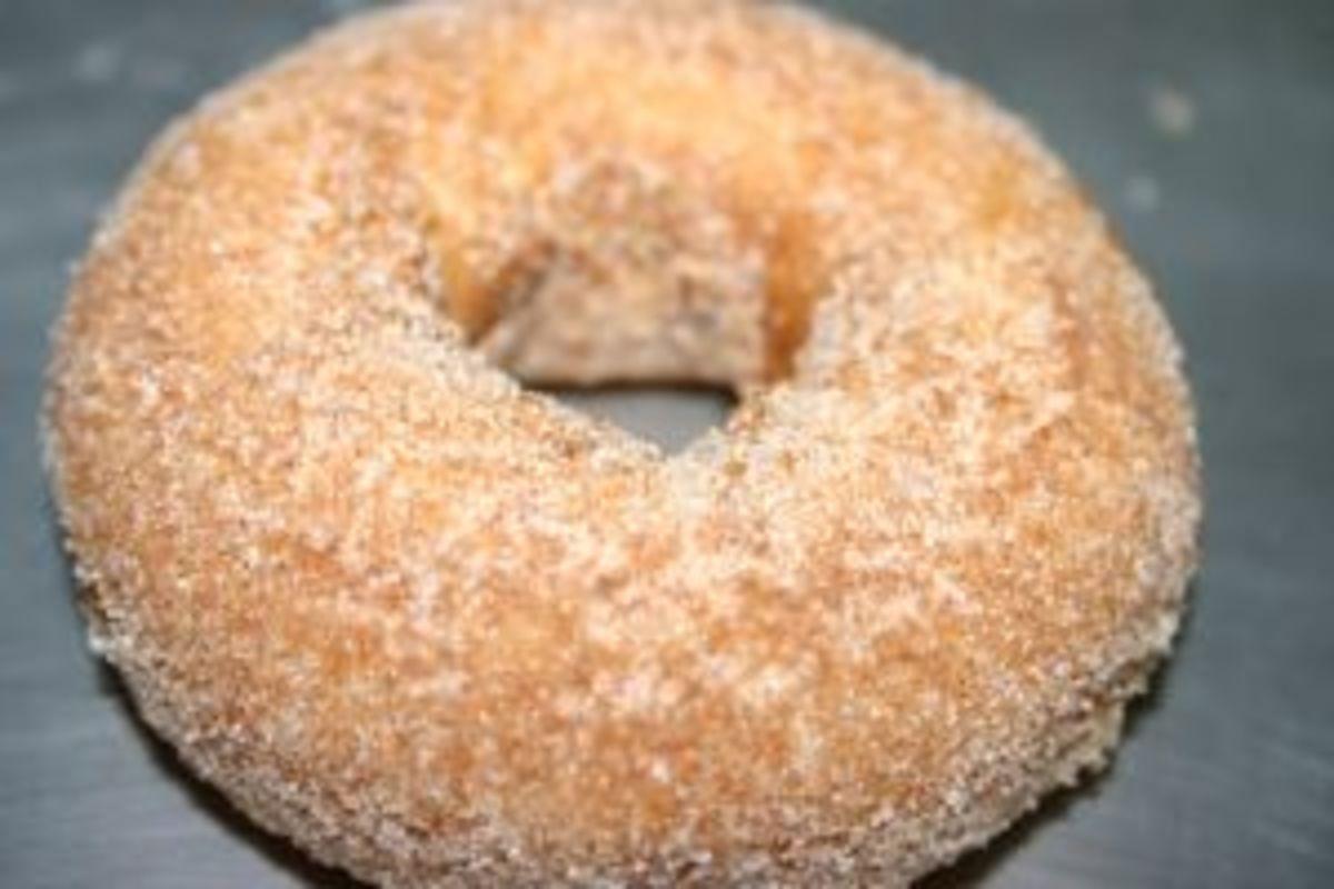 A doughnut rolled in cinnamon & sugar