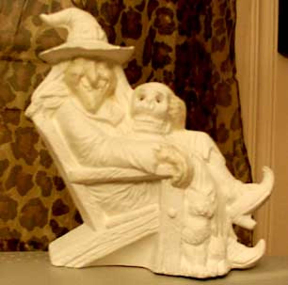 bisque ceramic witch with skull and cat in an Adirondack chair. Her face and hands are sealed with clear varnish. Next time, I'll use a bit of color in it and not paint her skin.