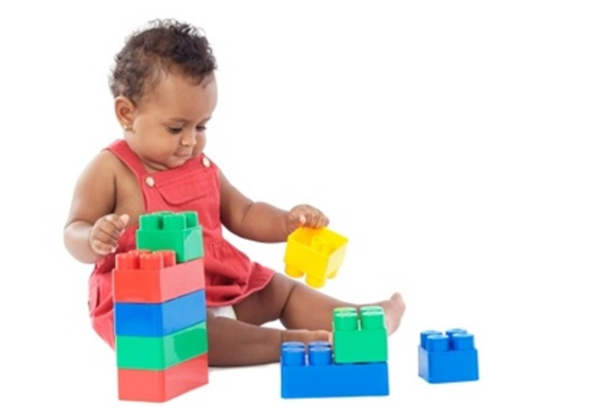 This young toddler is playing with giant building blocks (larger than Lego Duplo or Megabloks).
