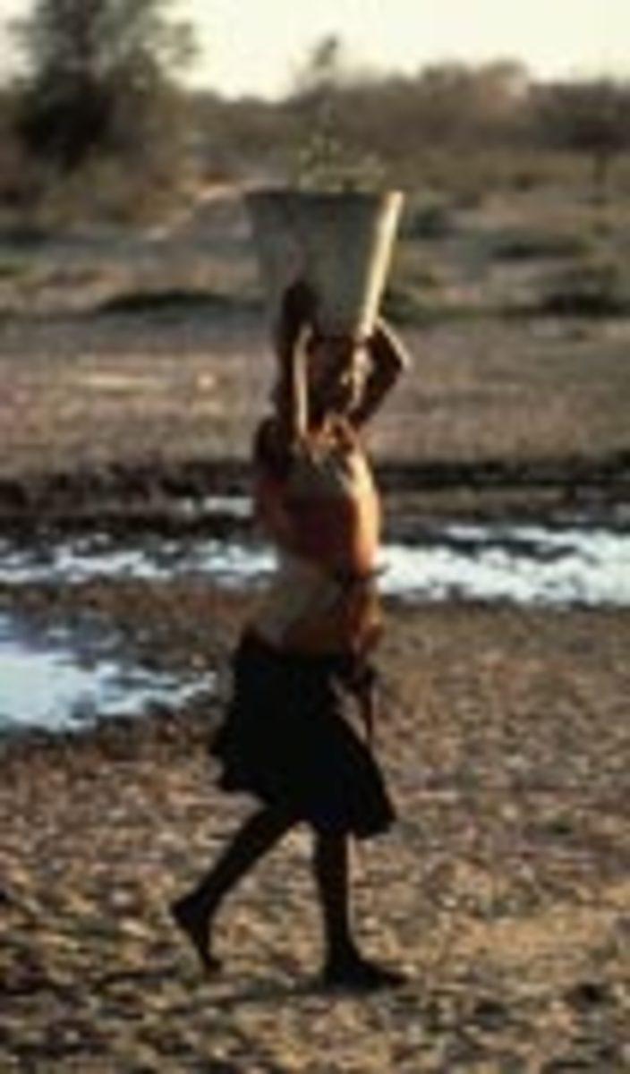 Bushman woman carrying water