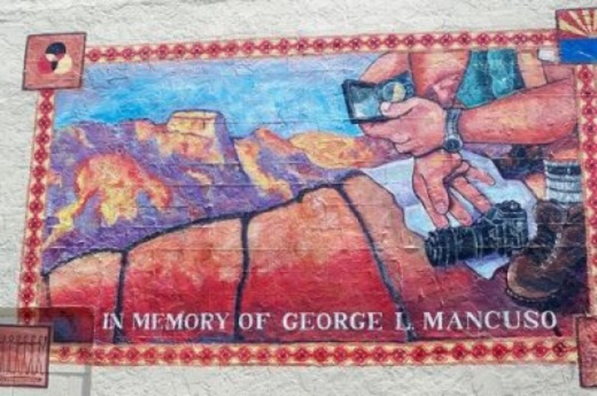 A mural in memory of a famous local photographer on the side of the Peace Surpluss building on Route 66