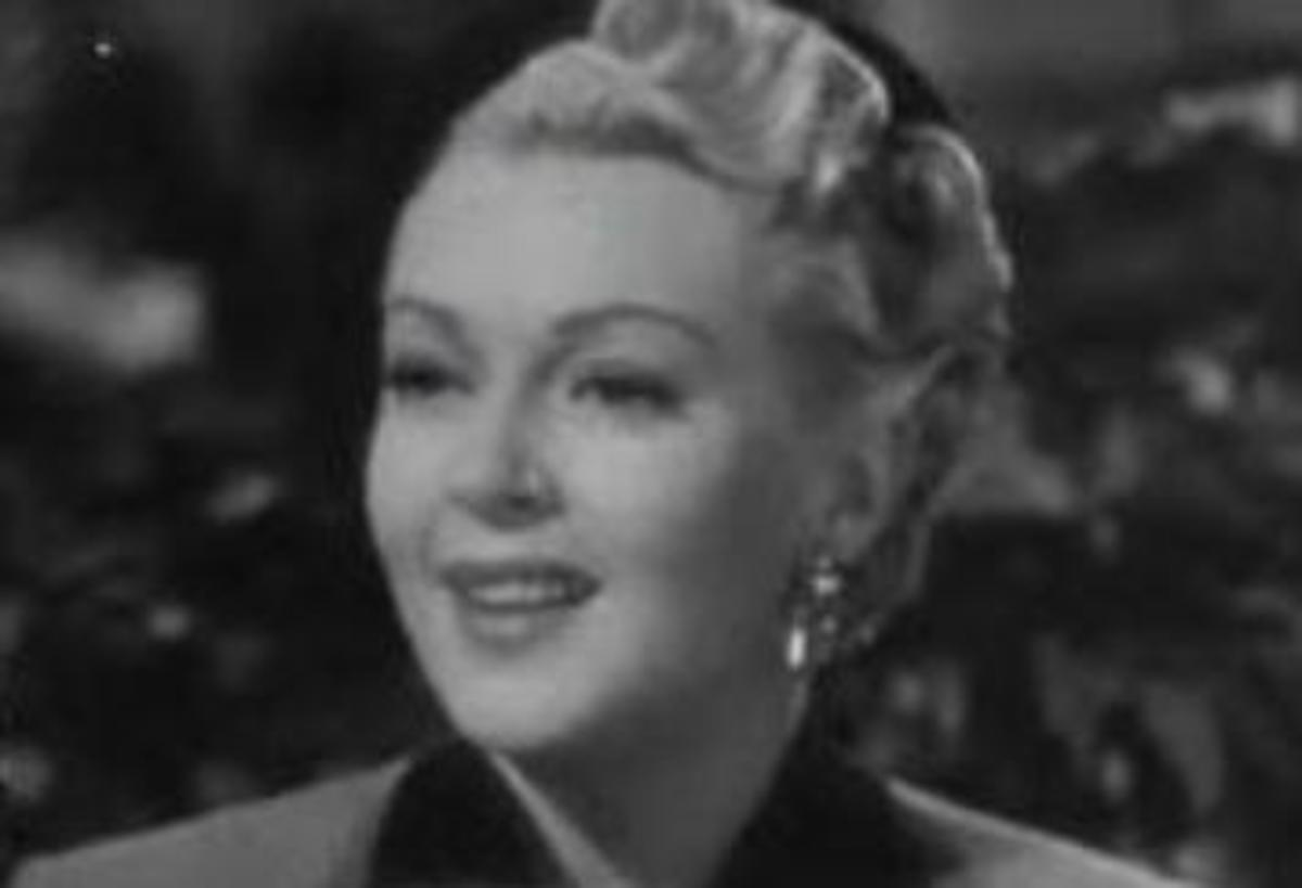 Lana Turner's round face is made more elegant by having her hair swept up and back.