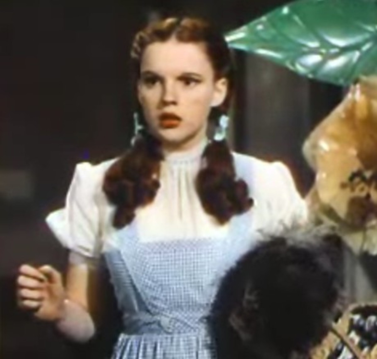 Judy Garland's face doesn't look very long in the Wizard of Oz.  With a close-cropped style around her head, her braids fluff out over her chest--this makes her face look round, like that of the young girl she's playing.