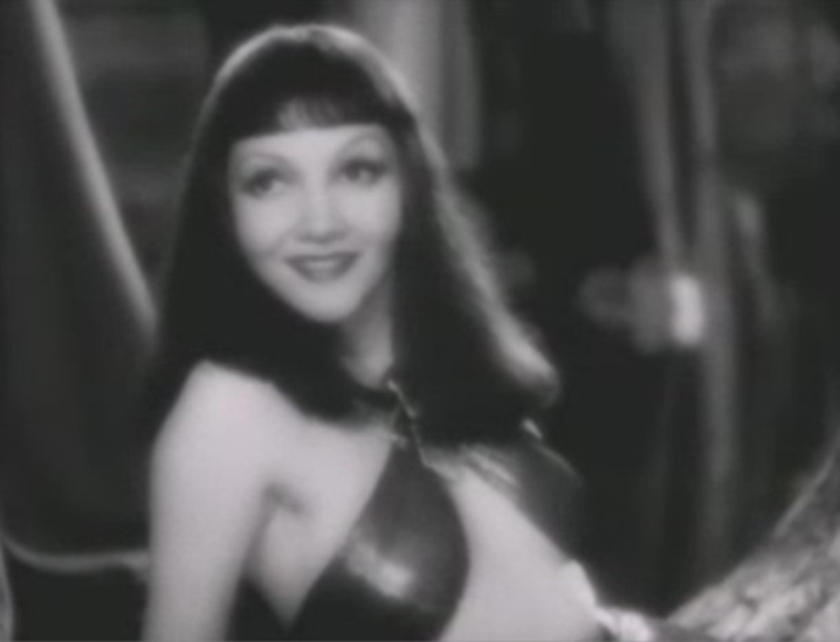 Claudette Colbert's face looks so nice and long with this long hair.  The bangs cropped midway down her forehead give the impression of a long forehead.  But hold on...