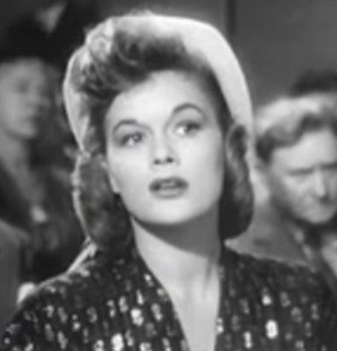 The square face of Jean Hagen is feminized by asymmetrical curls and a dashing wave on her forehead.