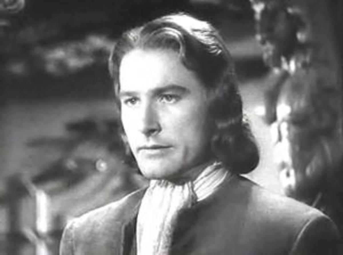 Errol Flynn's squarish face is made to look more even more square by the wavy, geometrical hairstyle that ends in both vertical and horizontal line with his chin.
