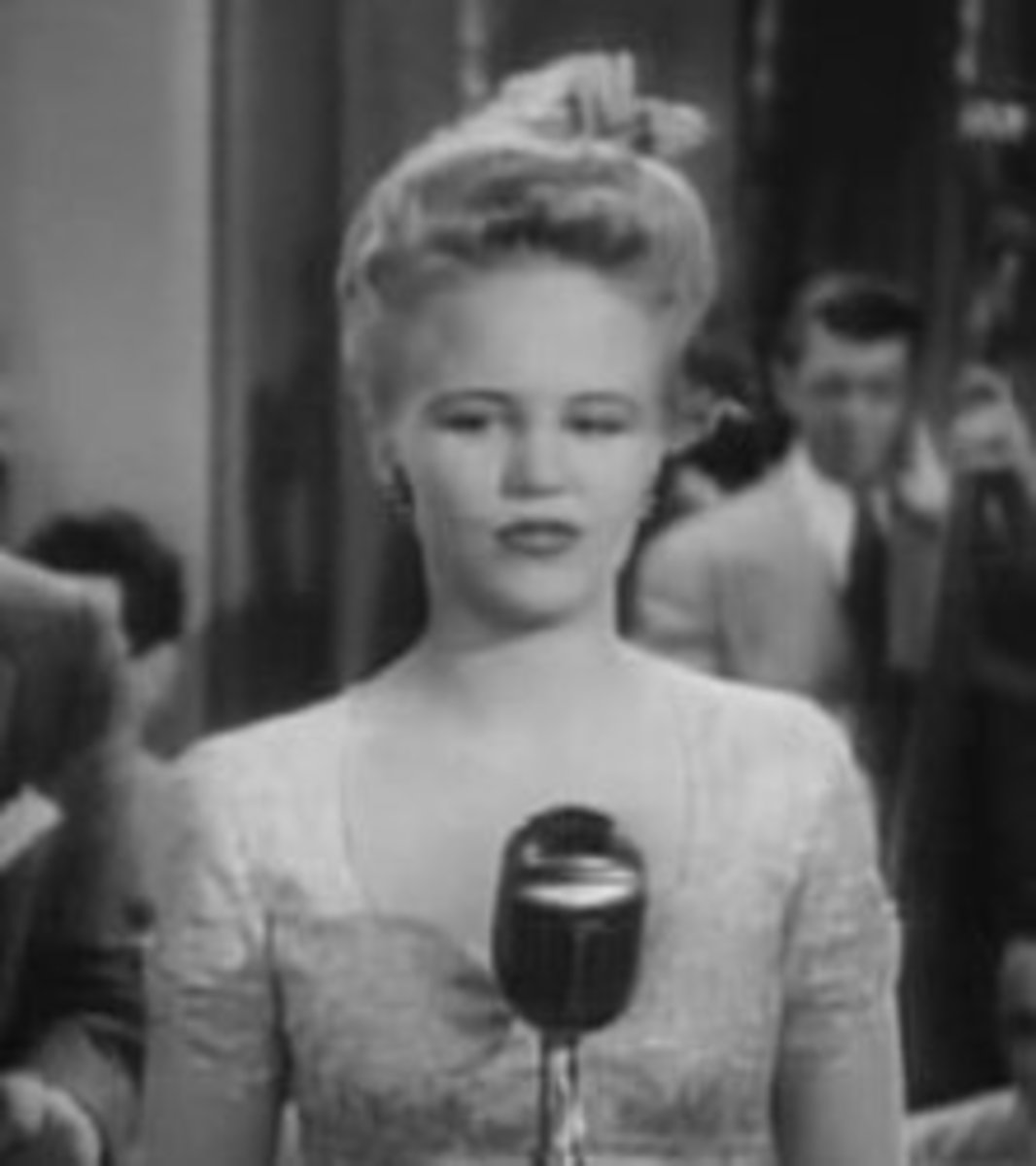 Peggy Lee's long face is emphasized here, but made more attractive by broadening the top of her head and drawing the eye to her broad forehead.
