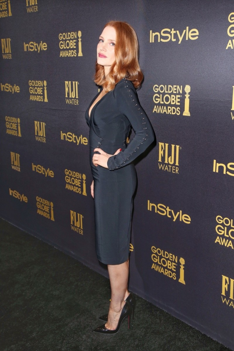 Jessica Chastain in a curve hugging black silk dress and pointy toe Louboutin pumps