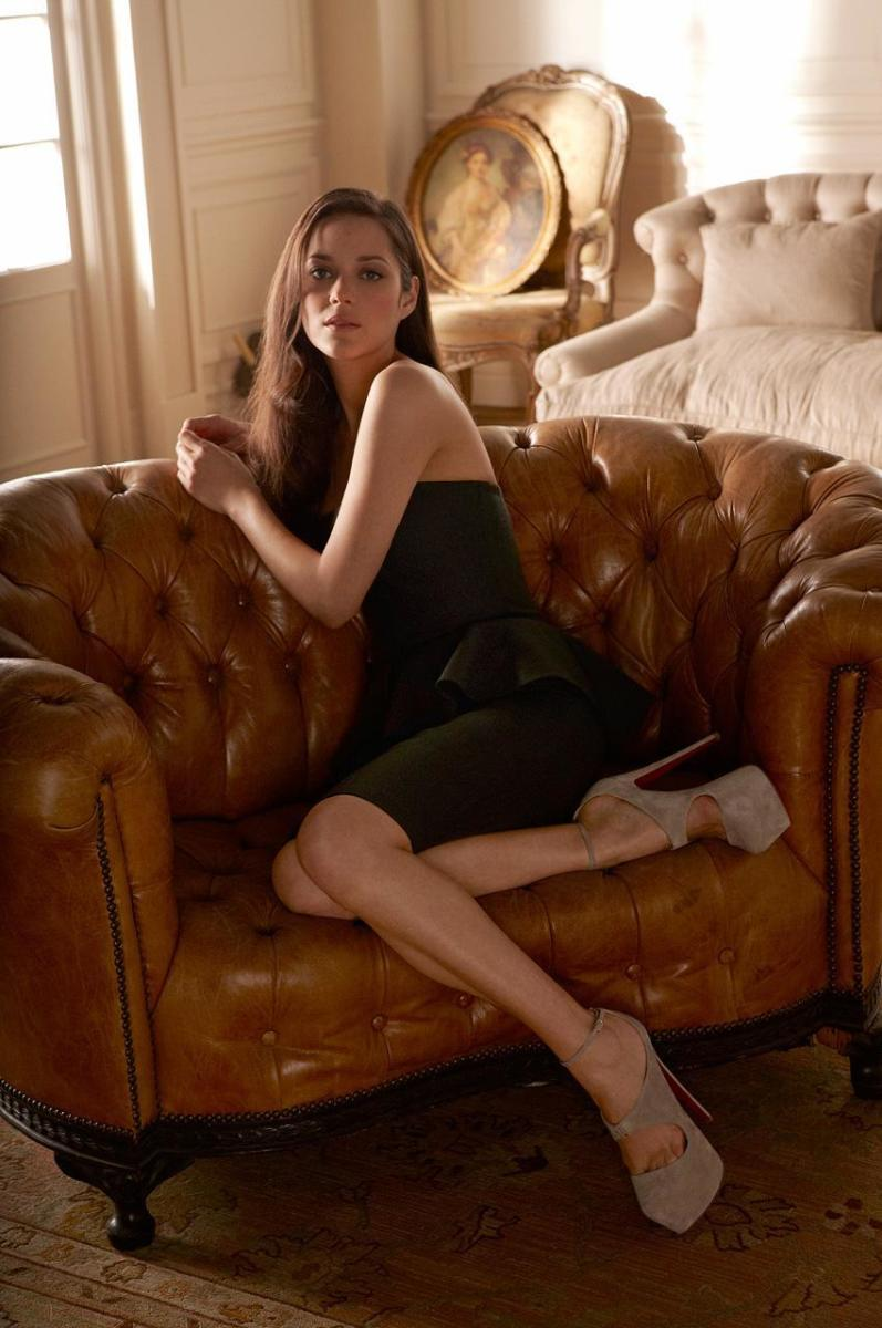 Marion Cottilard curved up on the sofa in a little black dress and sky high suede Louboutin stilettos