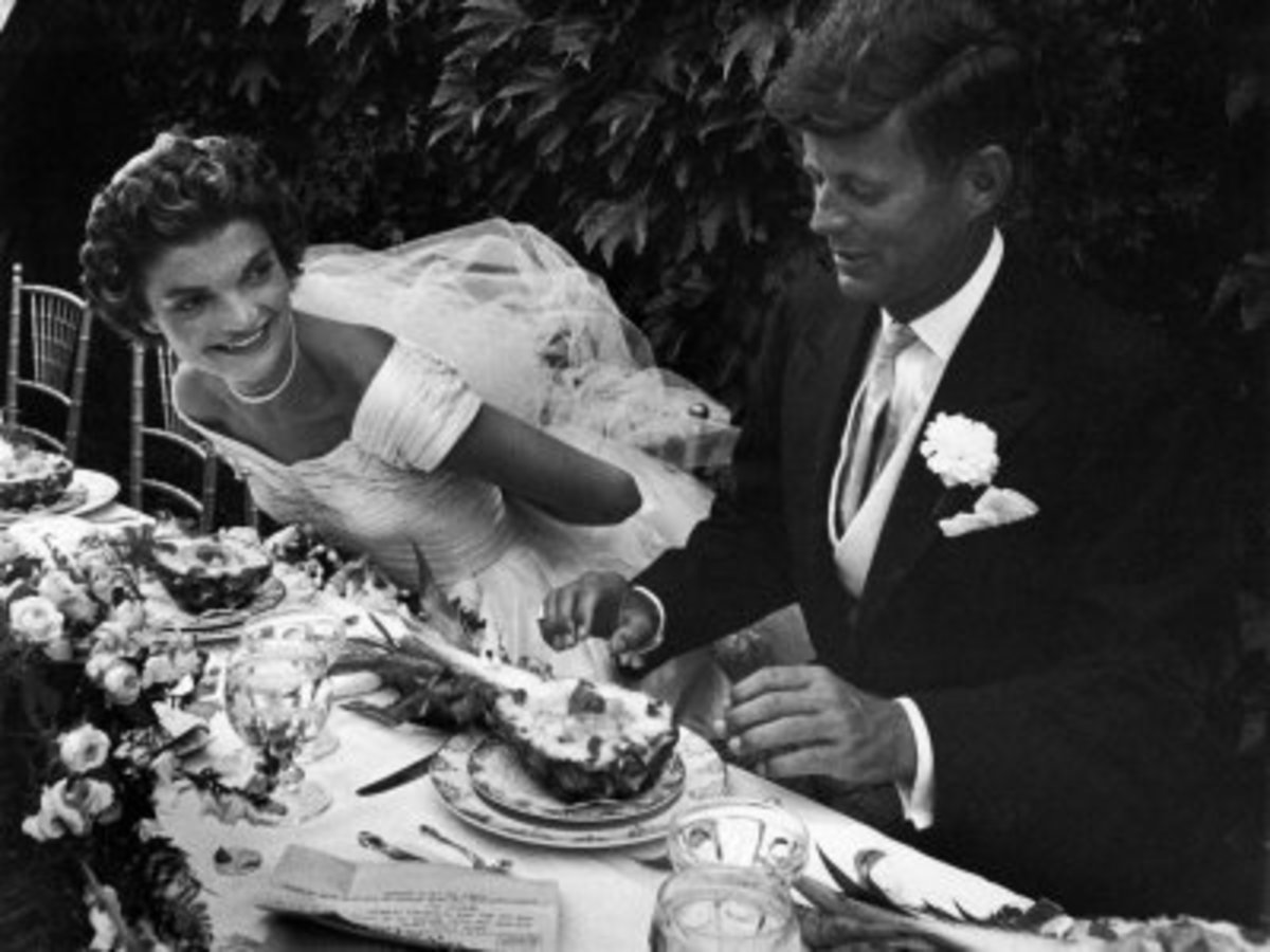 Jackie Kennedy in her wedding gown sitting next to JFK in his tuxedo