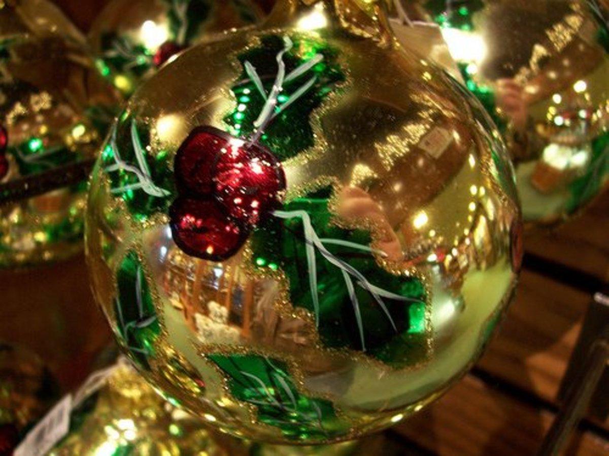A mistletoe Christmas bulb, shining golden.