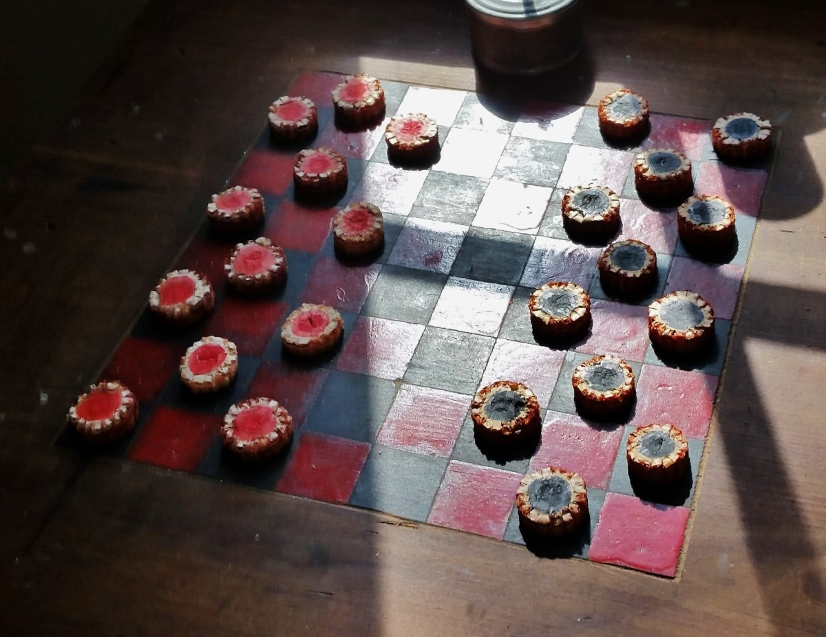 A homemade checker board with slices of corn cob as the checkers.