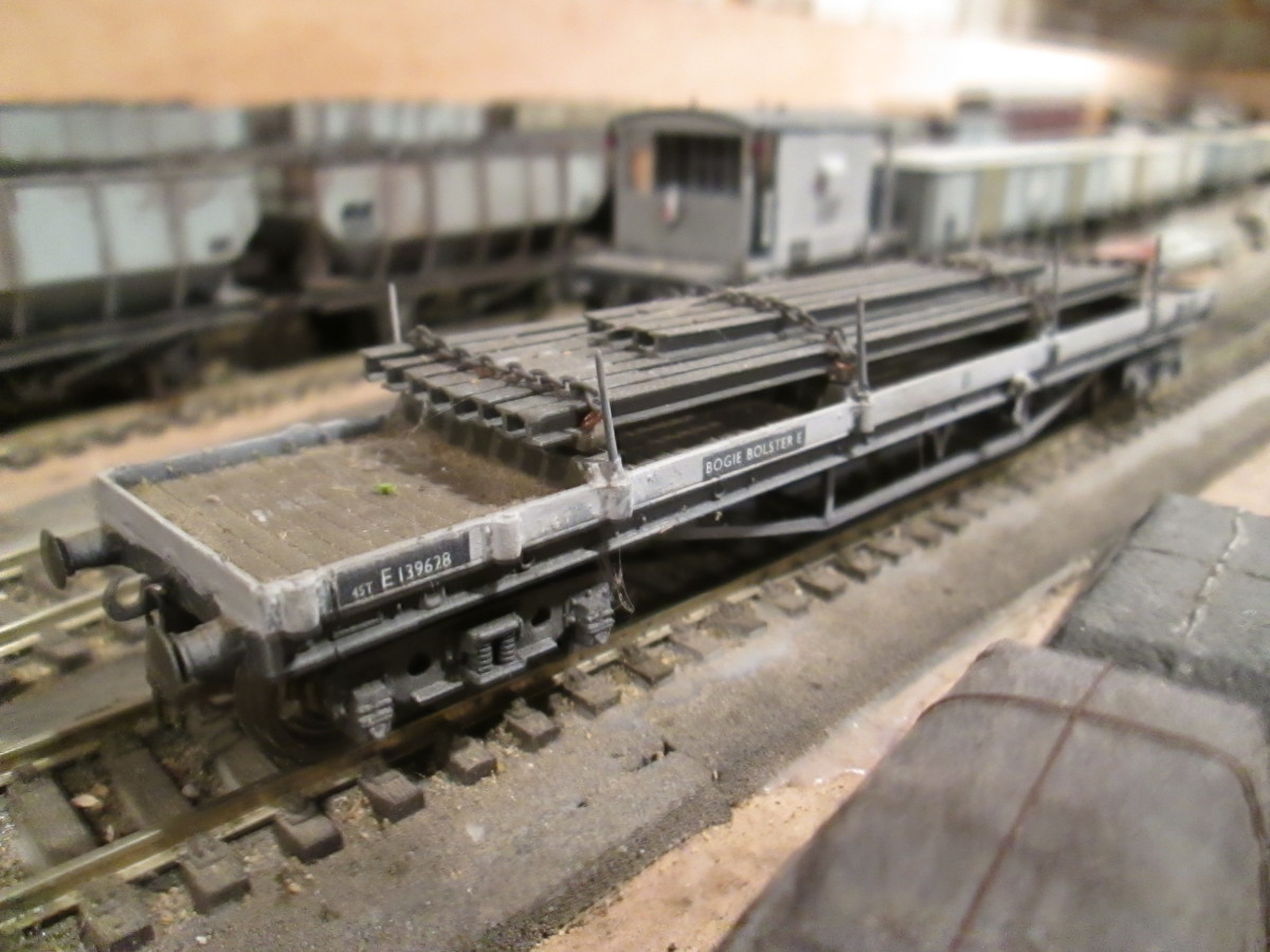 One of a trio of Bachmann ex-LMS Bogie Bolster wagons with chained square steel pipe load - one of two painted in early BR grey - see image top of page