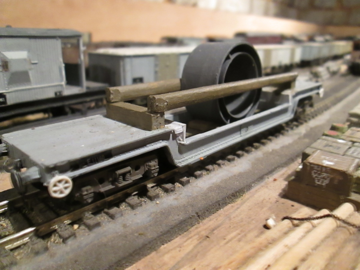 A ready-to-run Bogie Well wagon that started off as GW, modified, with brake wheels added from a plastic sprue and real wood bolsters to hold engineering parts (plastic Sellotape reel centre, painted engineering grey)