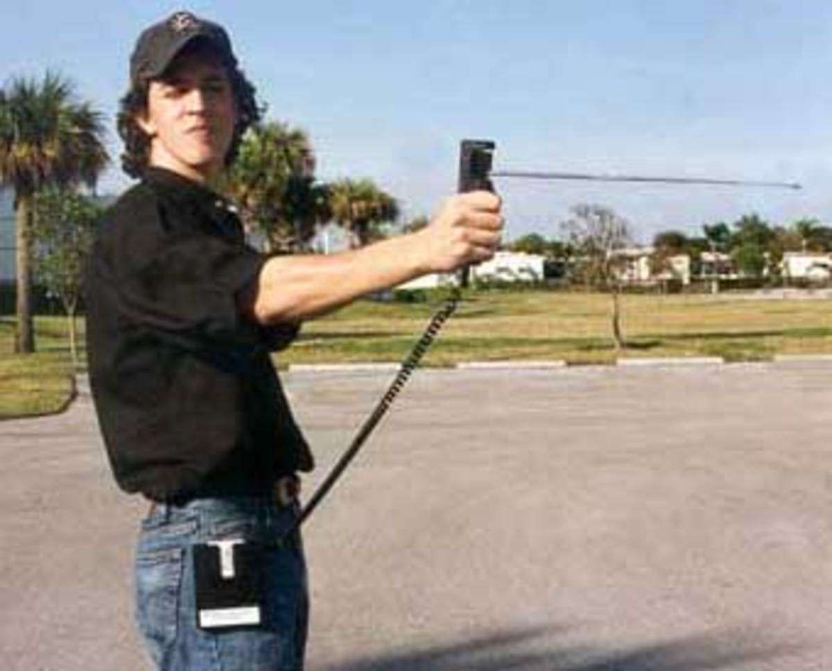 "Andrew Harter (Skeptics Society)  ""aiming"" a Quadro Tracker, note the free swirvel antenna  on the hand-held portion, and a belt/pocket module connected by a wire. (We'll get back to that)"