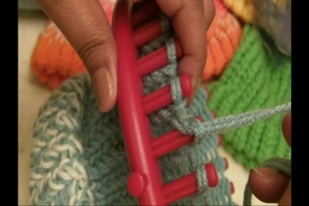 Use the yarn on the needle to pull of the yarn on the peg.