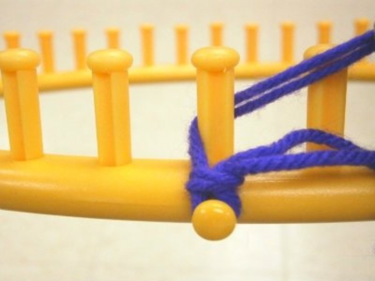 Pull the strands back behind the first peg and out to the side, in front of the peg to the right of it.