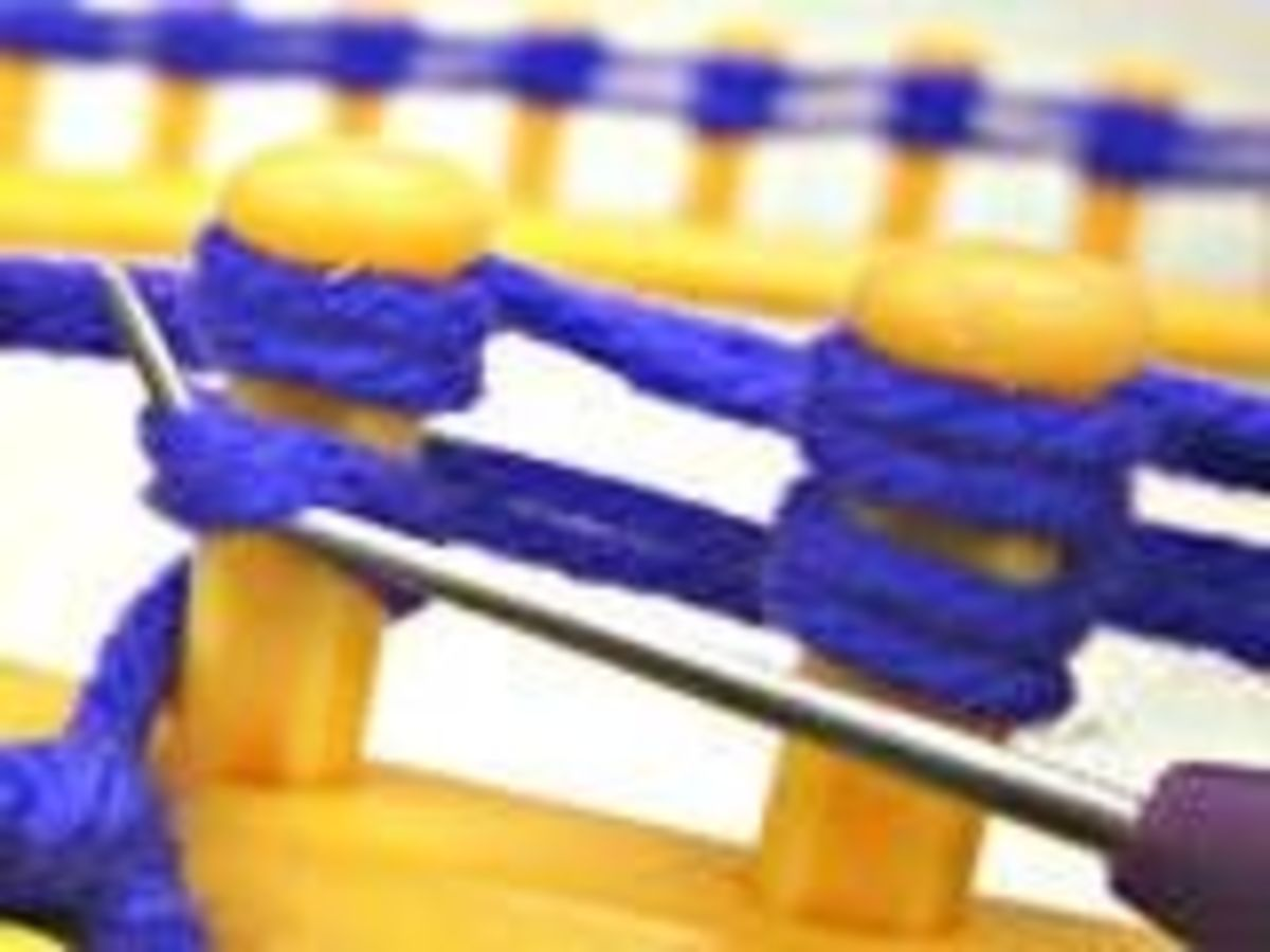 When you have completed to rows around the loom, get your hook and start with the first peg by slipping your hook under the bottom wrapped loop.