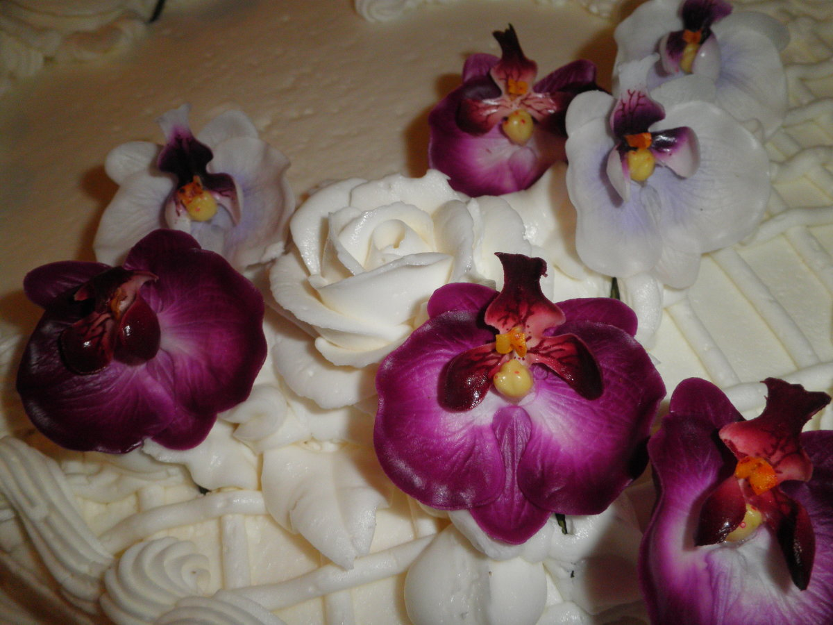 Orchids are the inspiration for this purple and gold white wedding cake.