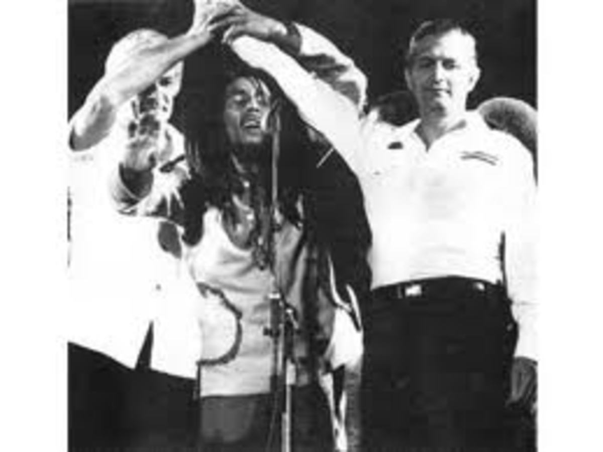 Bob Marley unite two warring factions JLP and PNP at his 1978 One Love Peace Concert. This is after they tried to kill him. Symbolic of uniting communism and capitalism.